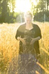 Pregnant woman holding her belly in a field of golden wheat