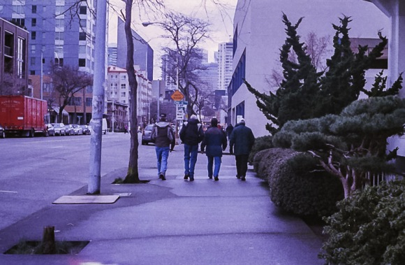 men walking down a sidewalk on Expired Kodak Gold Film